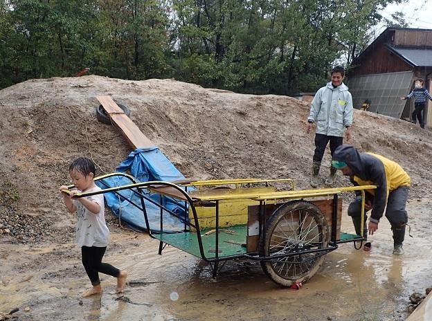 薪を運ぶためにリヤカーを曳く子ども
