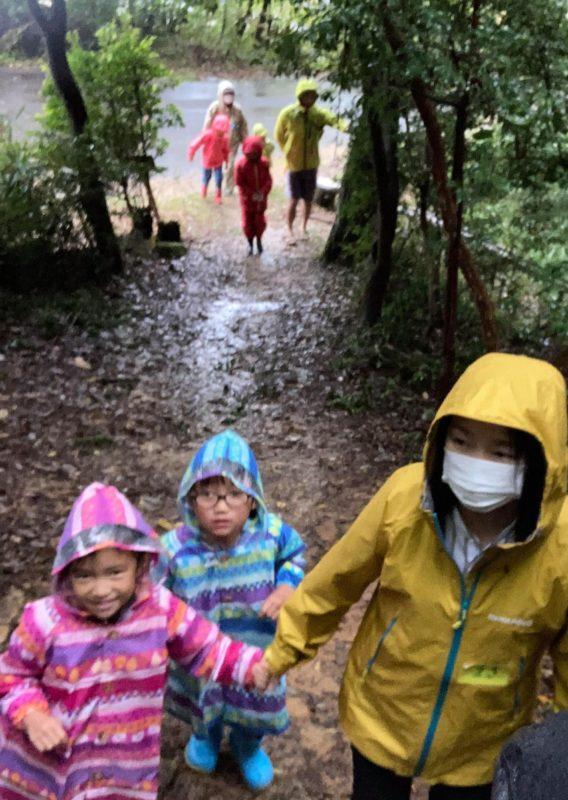 雨の中、演習林の見晴らし岩を目指す子どもたち