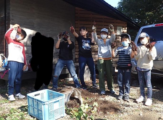 収穫したサツマイモを手にする子どもたち