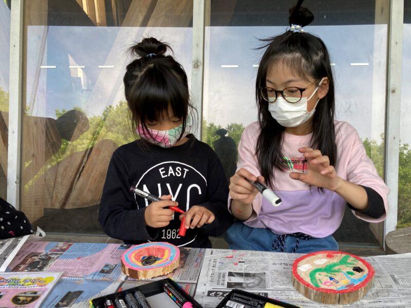 輪切りした丸太に絵を描く子ども