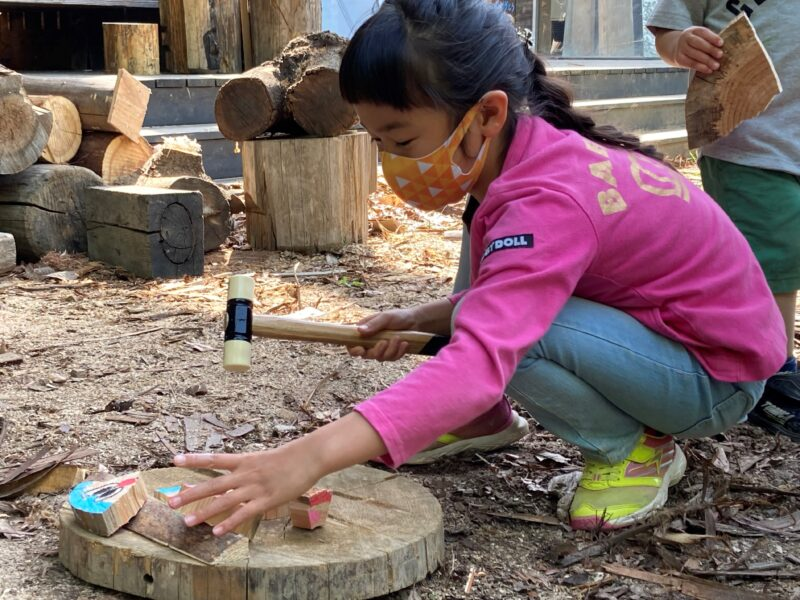 ハンマーで輪切りした丸太を割る女の子