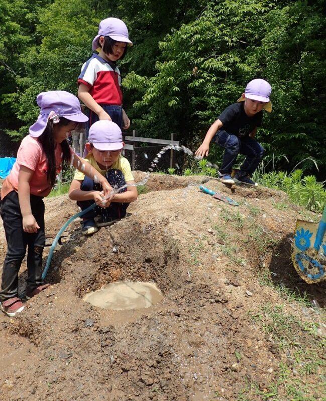 穴を掘って水をためる子どもたち